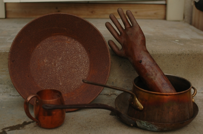 rusty gold pan, copper mug, pots, and hand mold for rubber gloves