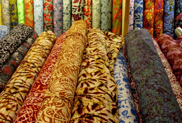 the store front has an array of cotton and silk batik for sale.